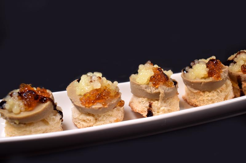 Canapés de micuit de pato con esferificaciones de vermut y manzana.